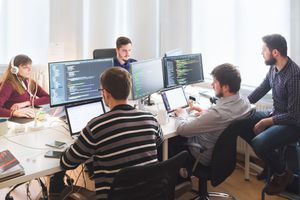 Software development team working in the office with big monitors