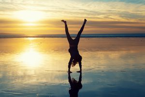 Silhouette of a woman doing cartwheels on the beach at sunset