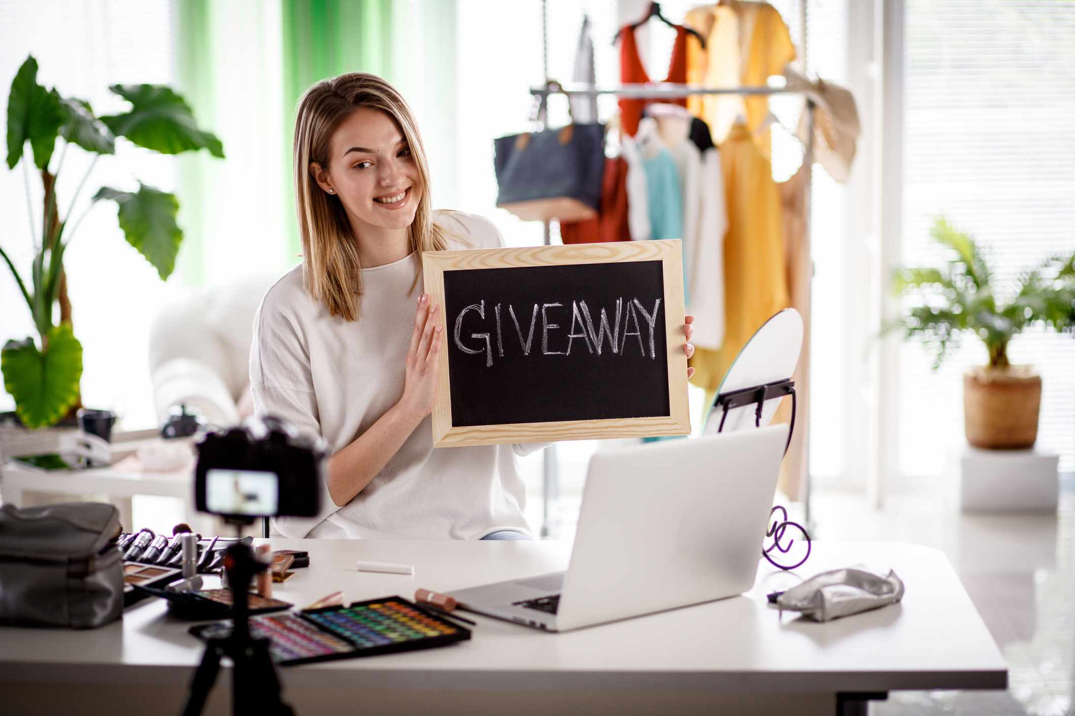 Beauty and fashion vlogger creating a giveaway campaign at home. Make-up products are in front of her, clothes are in the background.