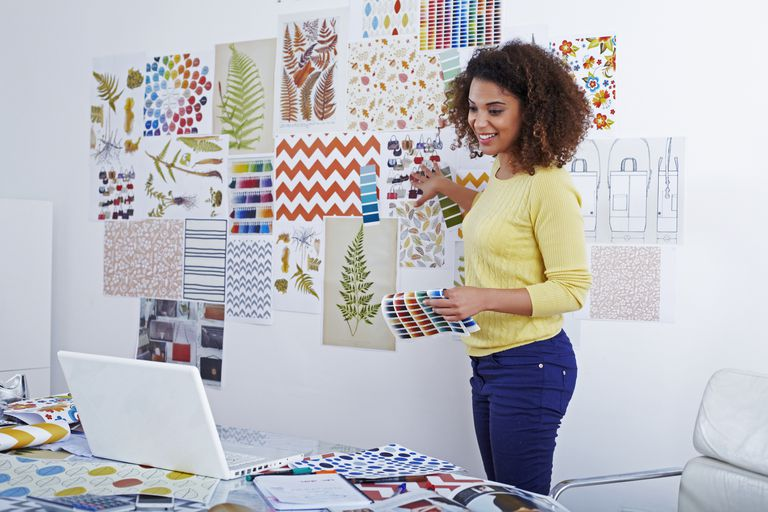 Woman standing in room with designs on wall in front of computer