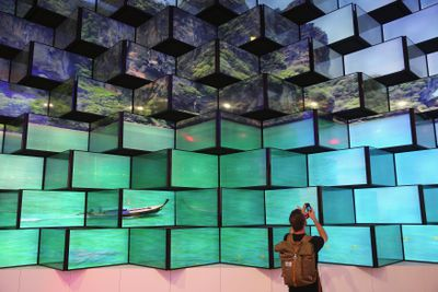 A visitor looks at LED televisions on display