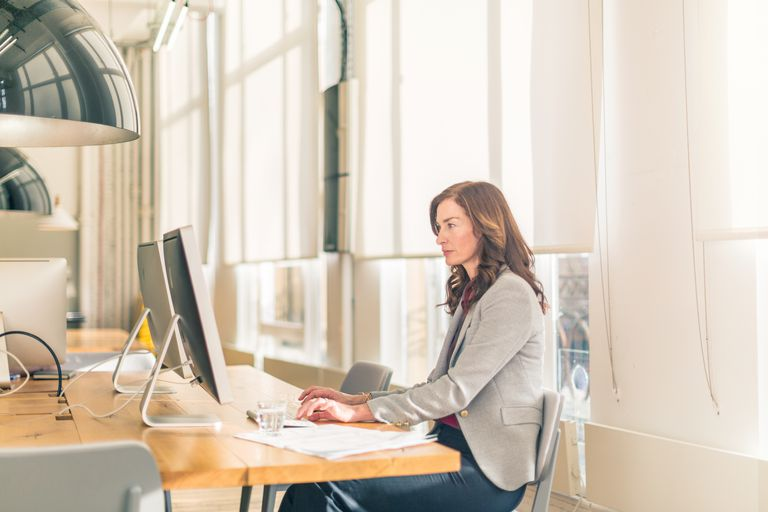 Woman sitting in office at desk.