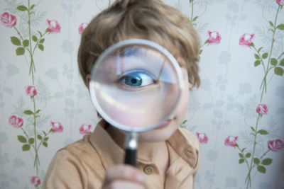 Kid looking at you through a big magnifying glass