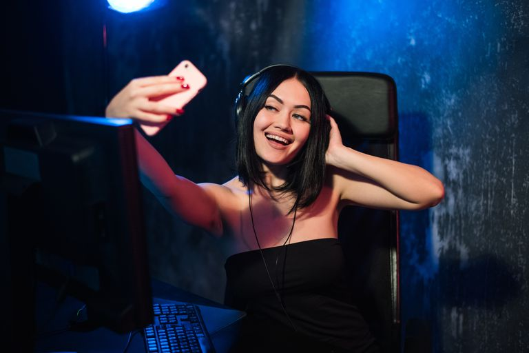 A woman takes a selfie while at her gaming PC.