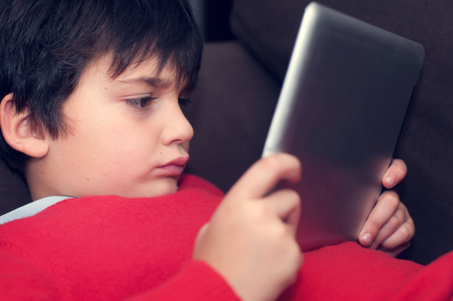 Boy reading with tablet