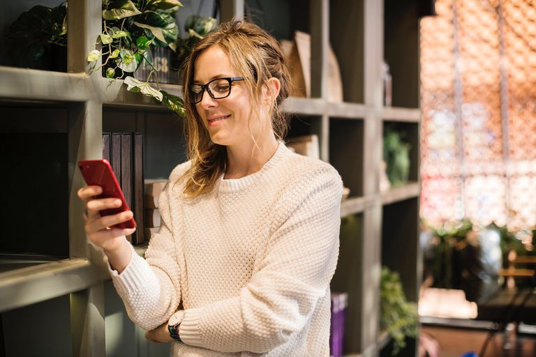 A stock photo of a woman standing next to a bookshelf holding and staring at a smartphone in her hand.