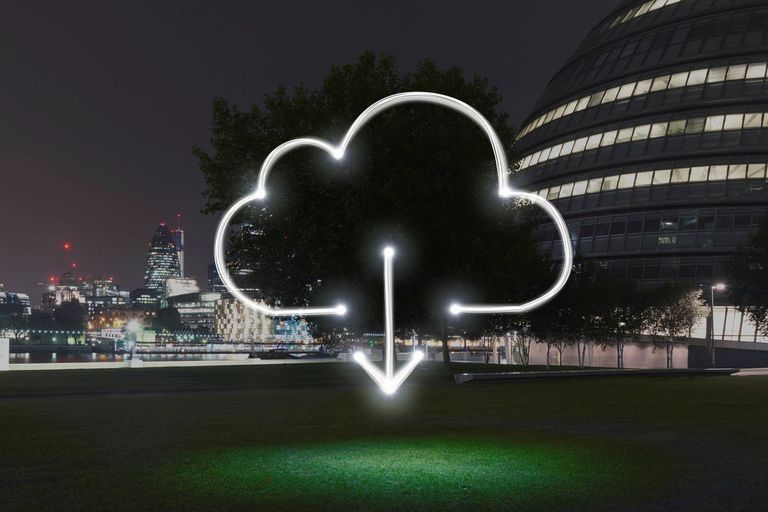 A cloud download symbol transposed over a tree in an urban setting