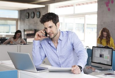 A businessman sitting at his desk and talking on his iPhone while looking at his Macbook.