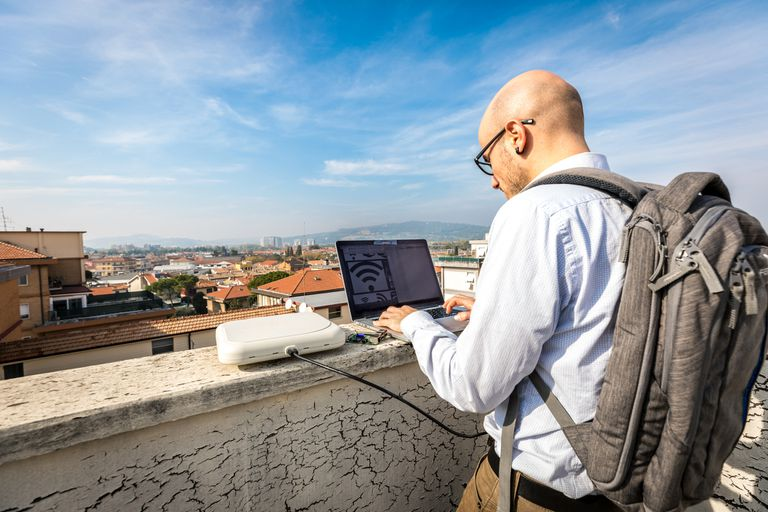 A man with a backpack using Wi-Fi on his laptop
