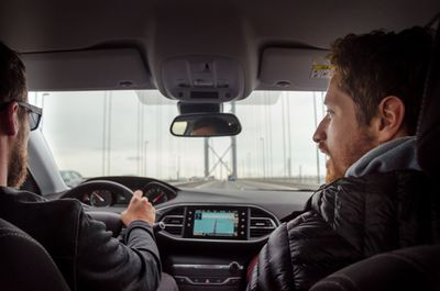 Driver and passenger driving across bridge in car