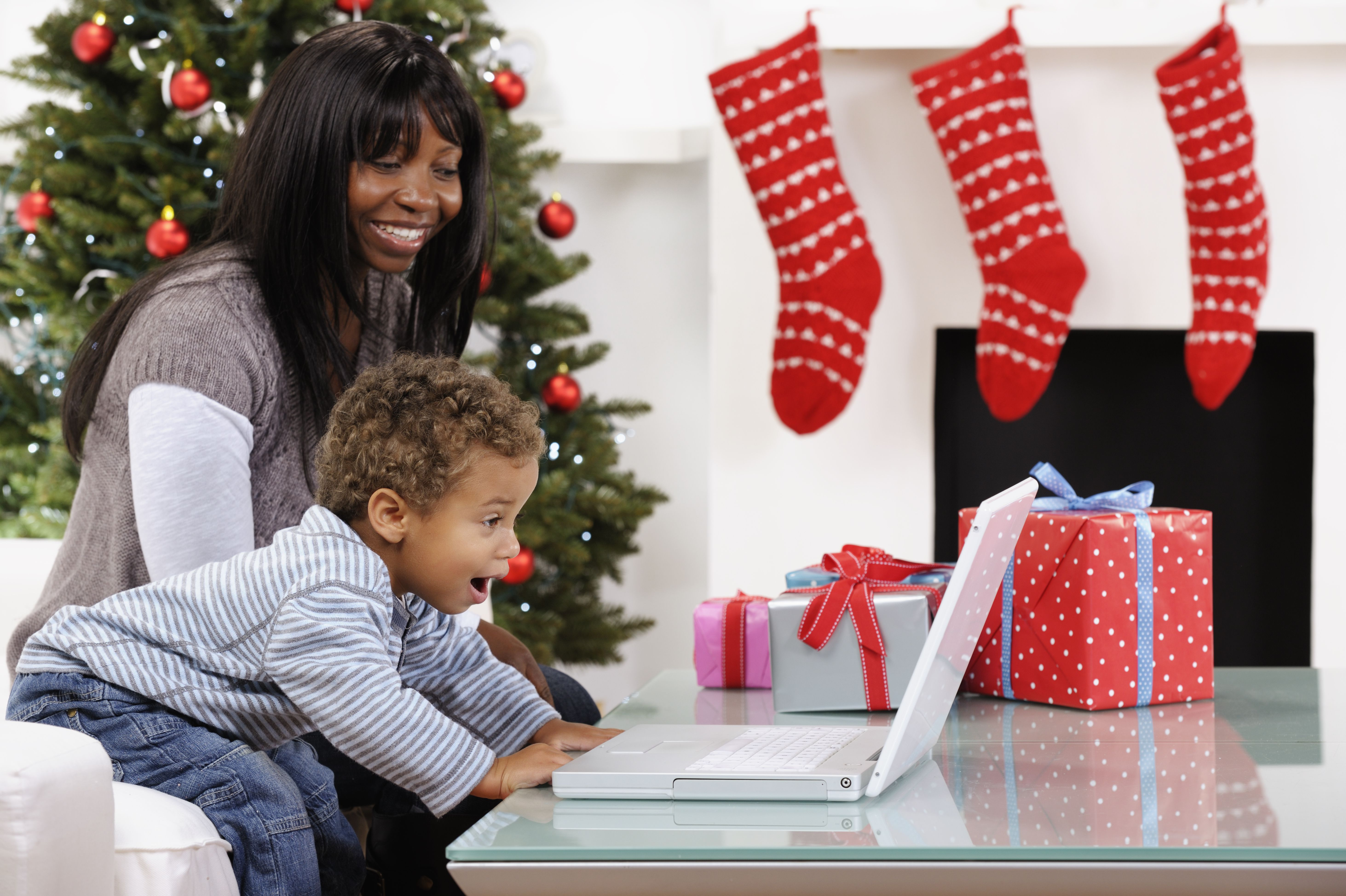 toddler excited while using computer with mother at christmas - Best Christmas Pandora Station