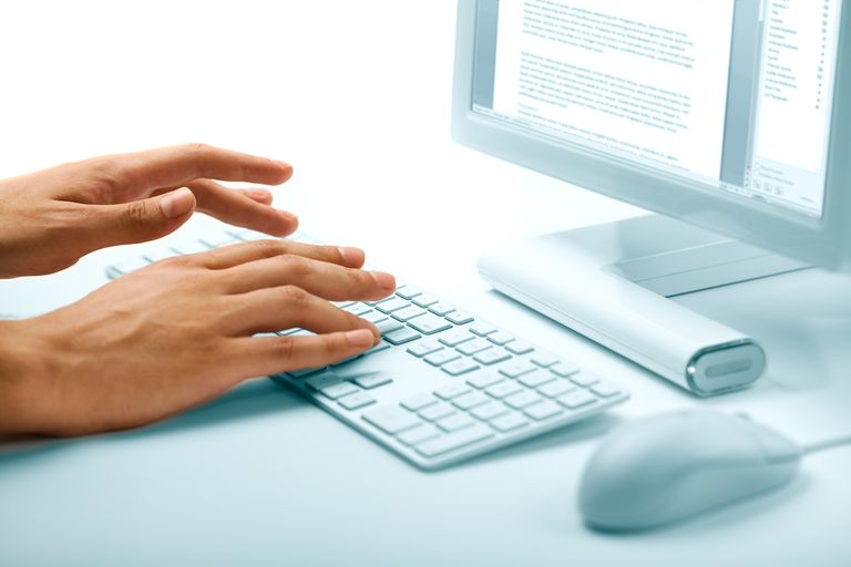 Hands typing on keyboard in word processing program
