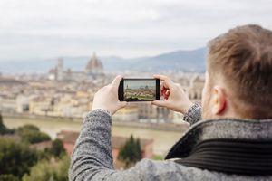 Tourist taking photo of city on smartphone