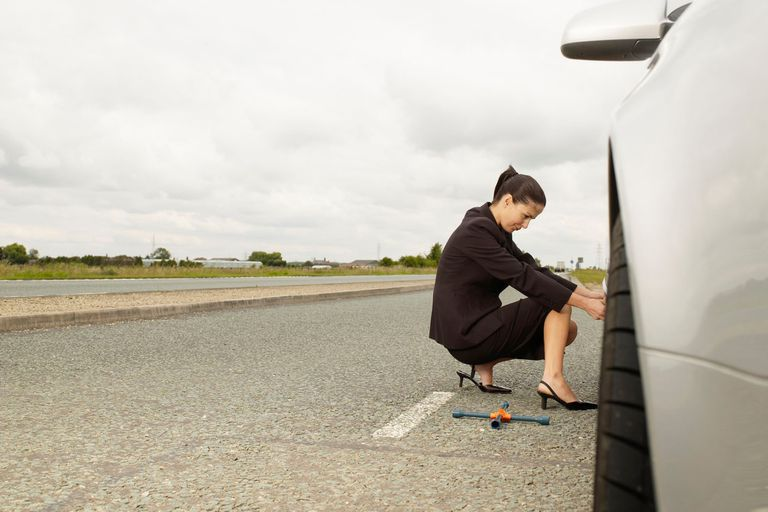 lady in business attire fixing a flat tire