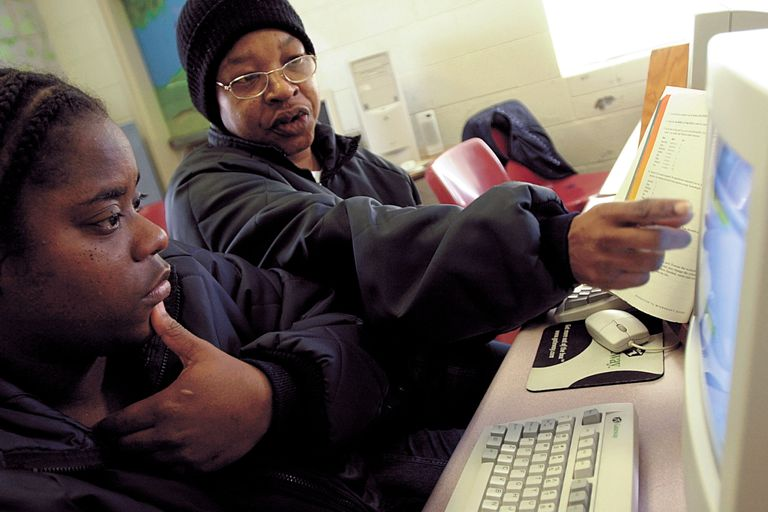 Monique Peterson of San Diego (L) gets some help learning to use the spreadsheet program Excel from fellow inmate Francine Lockley