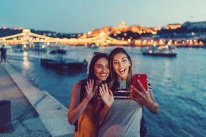 Two friends take a selfie in front of a bridge.