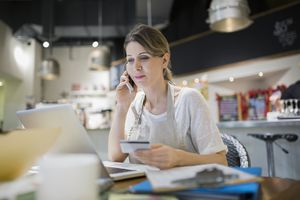 woman restaurant employee on phone at computer with credit card