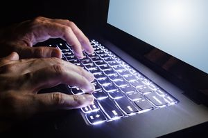 Hands typing on an illuminated keyboard on a laptop.