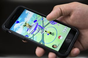 A person holds a phone with Pokemon Go open on the screen.