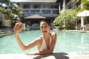 Woman using phone in pool