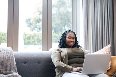 A woman sitting on a sofa with a laptop on her lap