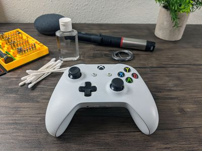 An Xbox One controller with tools to fix analog stick drift.