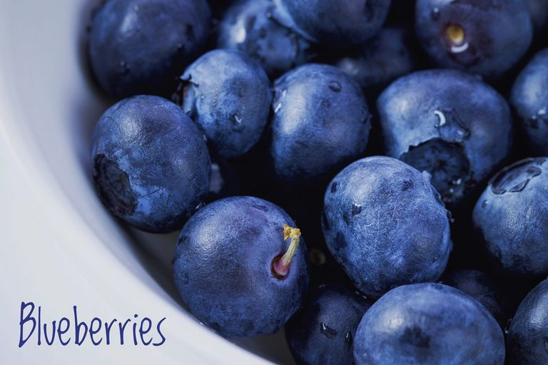 The color indigo shown on blueberries in a white bowl.