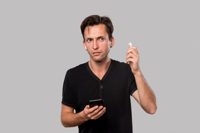 Man holding one AirPod outside his ear and making a face