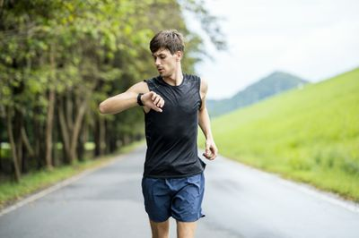 A jogging man standing surrounded by nature looking at his smartphone