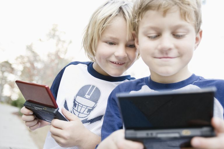 Brothers playing handheld video games