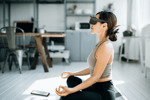 Someone doing yoga while wearing an HTC Vive Flow VR headset.