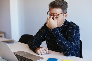 A frustrated man at his Mac laptop