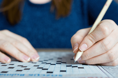 Screenshot of a woman filling out a crossword puzzle