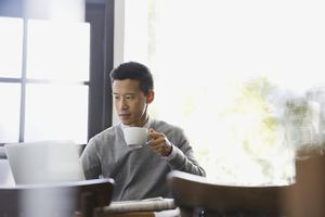 Businessman working on laptop in restaurant