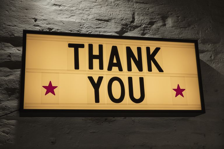 Close-up of Thank You signboard against gray wall