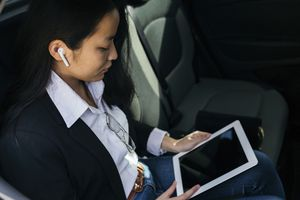 Woman using AirPods with iPad.