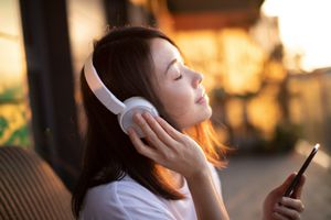 A woman listening to headphones on a porch while closing her eyes