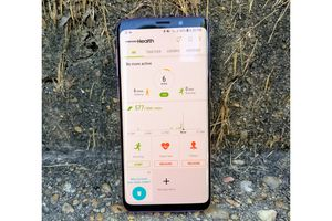 Phone sits on gravel, the Samsung Health app is pen and displaying recent activity.