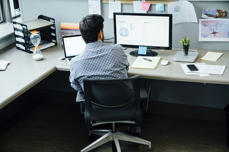 Businessman using laptop and computer to perform repetitive tasks