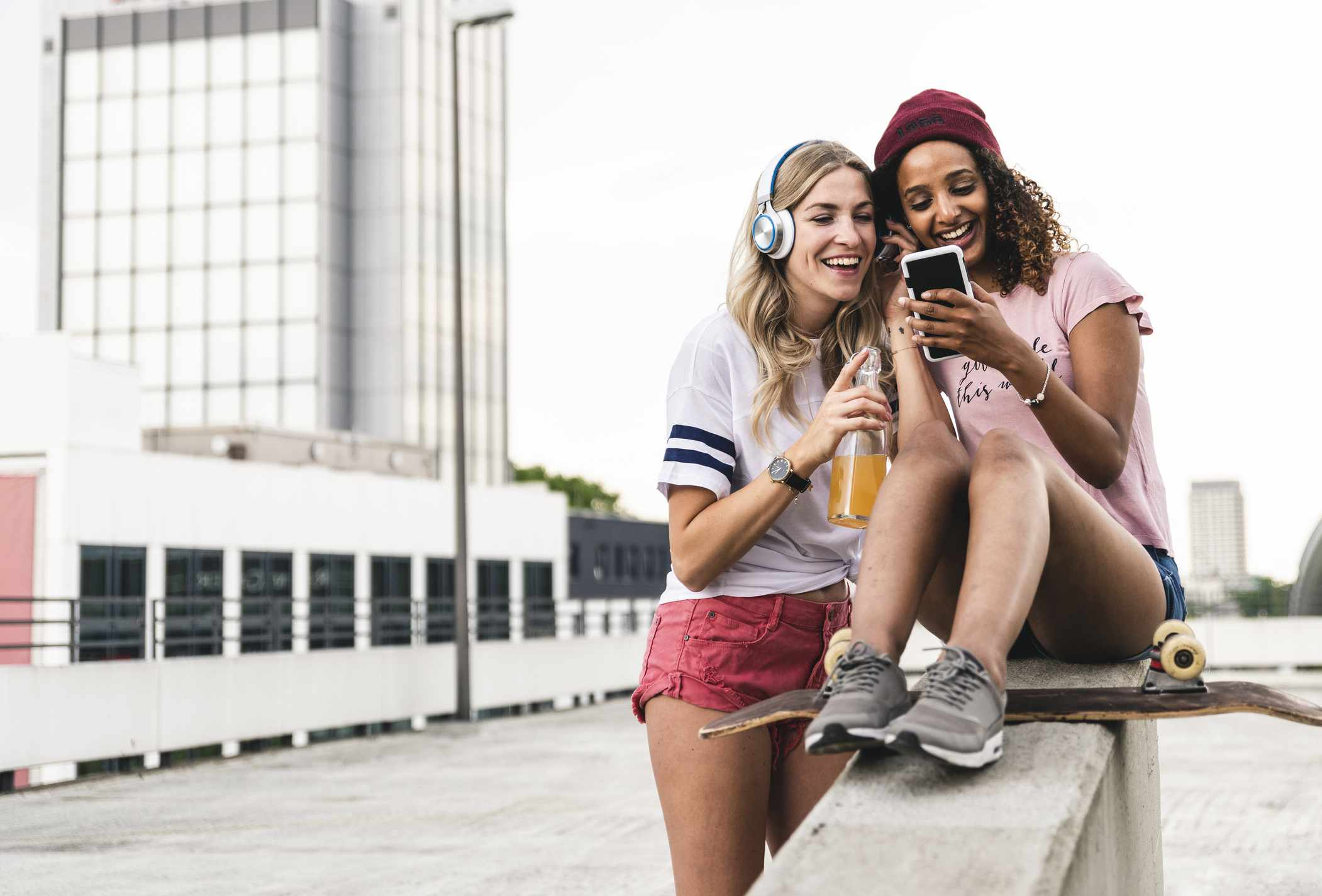 Two friends, with a skateboard, listening to music together.