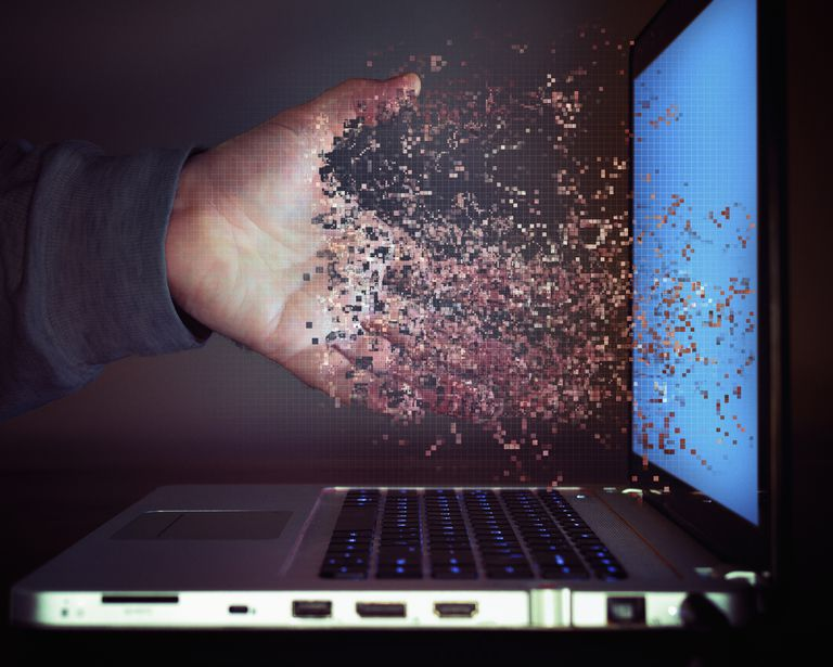 Pixelated hand dissolving into laptop screen