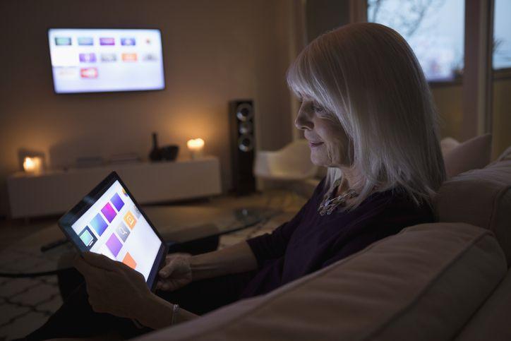 Person using smart TV apps on digital tablet on living room sofa