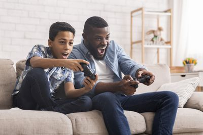 A father and son sit on a couch holding games controllers cheering at the screen
