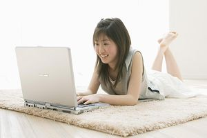 Girl lying on the carpet and using laptop in the room