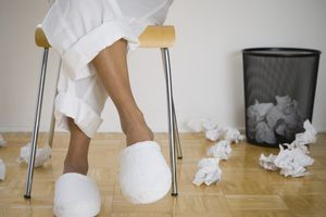 Woman sitting cross-legged in white slippers with balled up paper in and around wastepaper basket