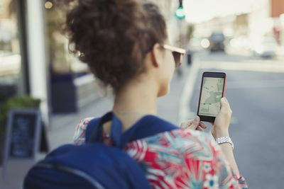 A woman using a map on the web browser of her smartphone as she navigates through a city.