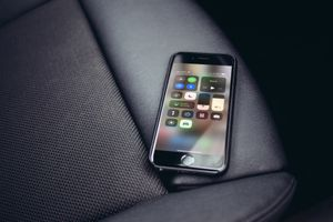 iPhone with Control Center onscreen in passenger seat of a car