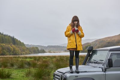Woman shooting photos from atop a car