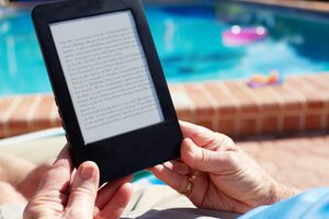 A person near a swimming pool reading a digital book