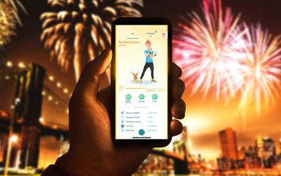 A man's hand holding an iPhone up in front of fireworks while checking his XP level in the Pokemon GO video game.